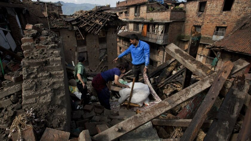 FILE - In this April 27, 2015 file photo a Nepalese family collects belongings from their home destr