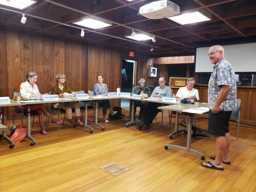 La Jolla Cove Swim Club co-chair Tom Hecker (standing) addresses the La Jolla Shores Association board seeking approval to move the Swim from The Cove to The Shores this year (and possibly next).
