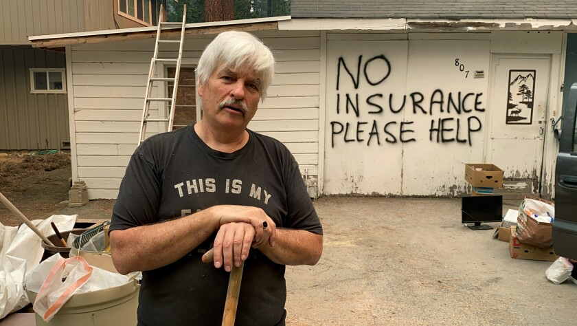Tod Johnson stands in front of his house in South Lake Tahoe, Calif., on Tuesday, Aug. 31, 2021, a day after the city was ordered to evacuate because of the fast-growing Caldor Fire. He spray-painted his house, which is not insured, hoping that firefighters would help save it if the fire reaches his neighborhood. (AP Photo/Terry Chea)