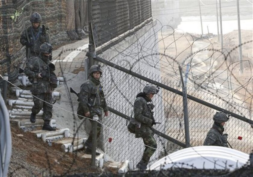 """South Korean Army soldiers patrol along a barbed-wire fence near the border village of Panmunjom in Paju, South Korea, Sunday, March 31, 2013. North Korea warned South Korea on Saturday that the Korean Peninsula had entered """"a state of war"""" and threatened to shut down a border factory complex that'"""