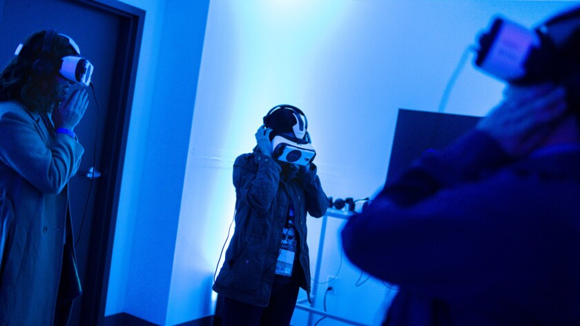 People watch virtual reality content produced by Vrse.Works, during a filmmaker welcome party on the second night of AFI.