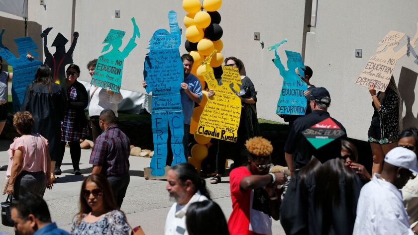 Demonstrators hold signs in support of Claudia Rueda, a Cal State L.A. student detained by Border Patrol in Boyle Heights on Thursday.