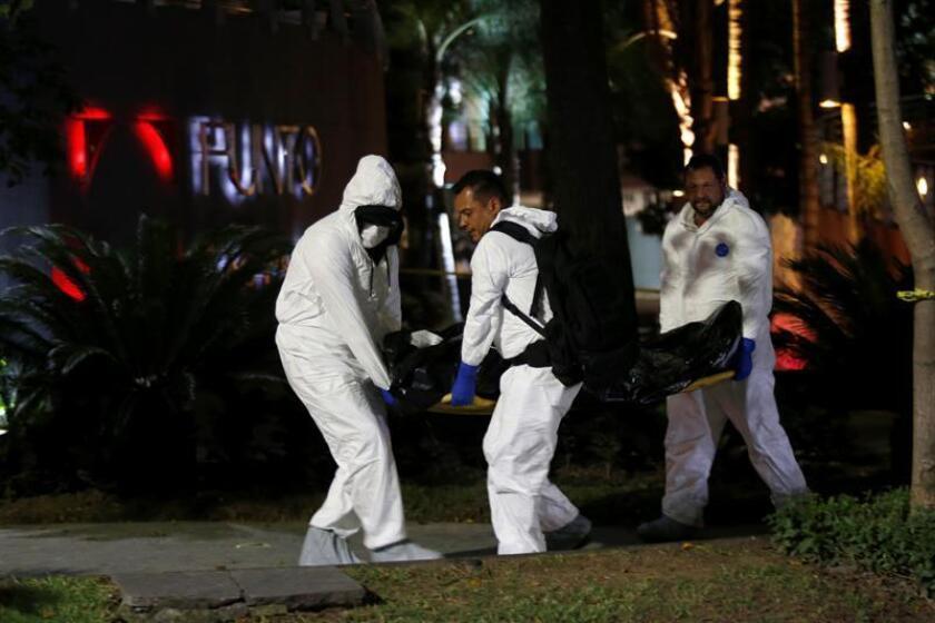 Fotografía fechada el 15 de agosto de 2018, que muestra a peritos forenses que cargan un cuerpo fuera de un centro comercial en el municipio de Zapopan, Jalisco (México). EFE