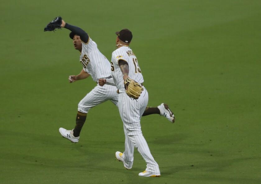 Ha-seong Kim catches a pop up behind third base as Manny Machado also gives chase.