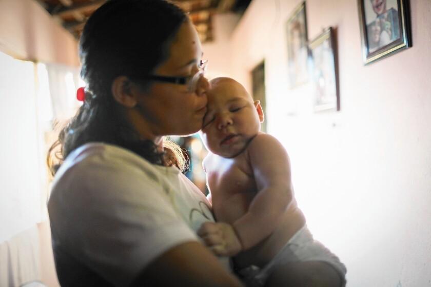 Mylene Helena Ferreira holds son David Henrique Ferreira, 5 months, in Recife, Brazil. David has microcephaly.