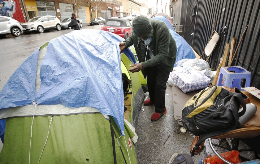 A man looks into his tent on L.A.'s skid row