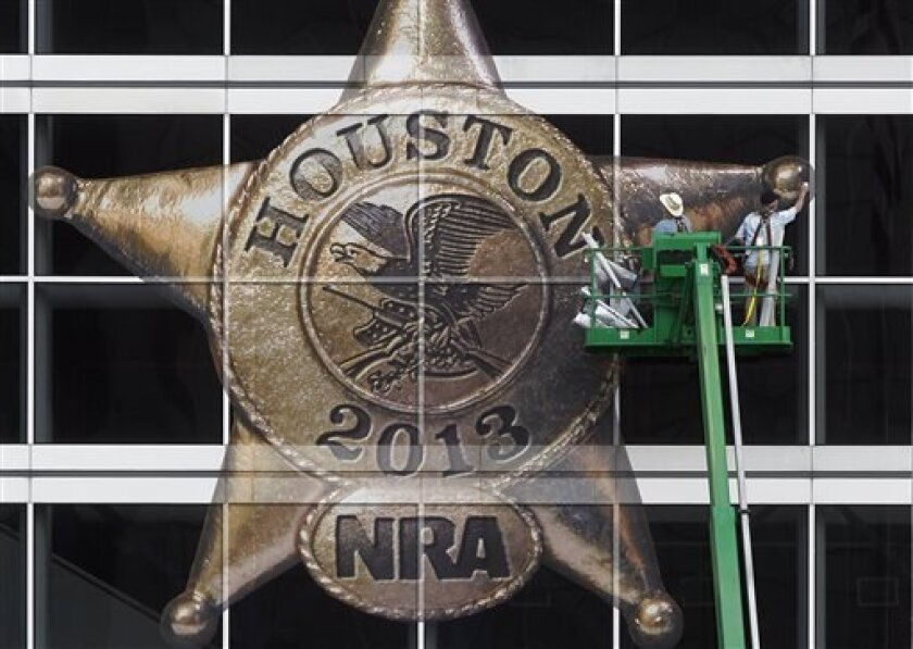 The National Rifle Association logo is placed on the George R. Brown Convention Center by Lynn Creel, left, and Don Reynolds of Display Graphics on Wednesday, May 1, 2013, in Houston. The 2013 NRA Annual Meetings and Exhibits is scheduled to being Friday. (AP Photo/Houston Chronicle, Johnny Hanson)