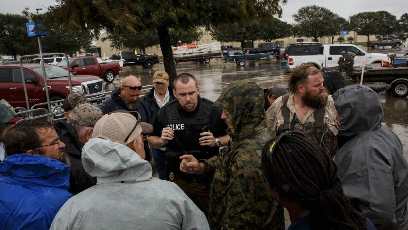 Volunteers from Fort Worth gather around Port Arthur Deputy Police Chief Cory Cole before they head