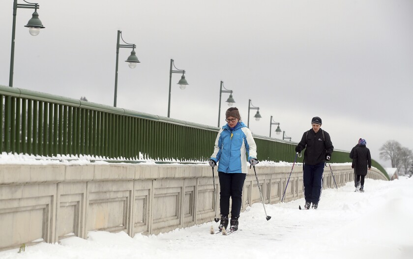 FILE - Erin Jaske and Scott Sandridge cross country ski across the Manette bridge in Bremerton, Wash., on a snowy day, in this Saturday, Feb. 13, 2021, file photo. During the pandemic, people around the world sought relief from lock downs and working from home in leisure sports. (Meegan M. Reid/Kitsap Sun via AP, File)/Kitsap Sun via AP