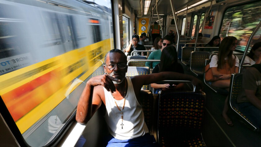 Jules Watkins of Los Angeles rides a Metro Expo Line train. Transportation registered broad job gains in August.