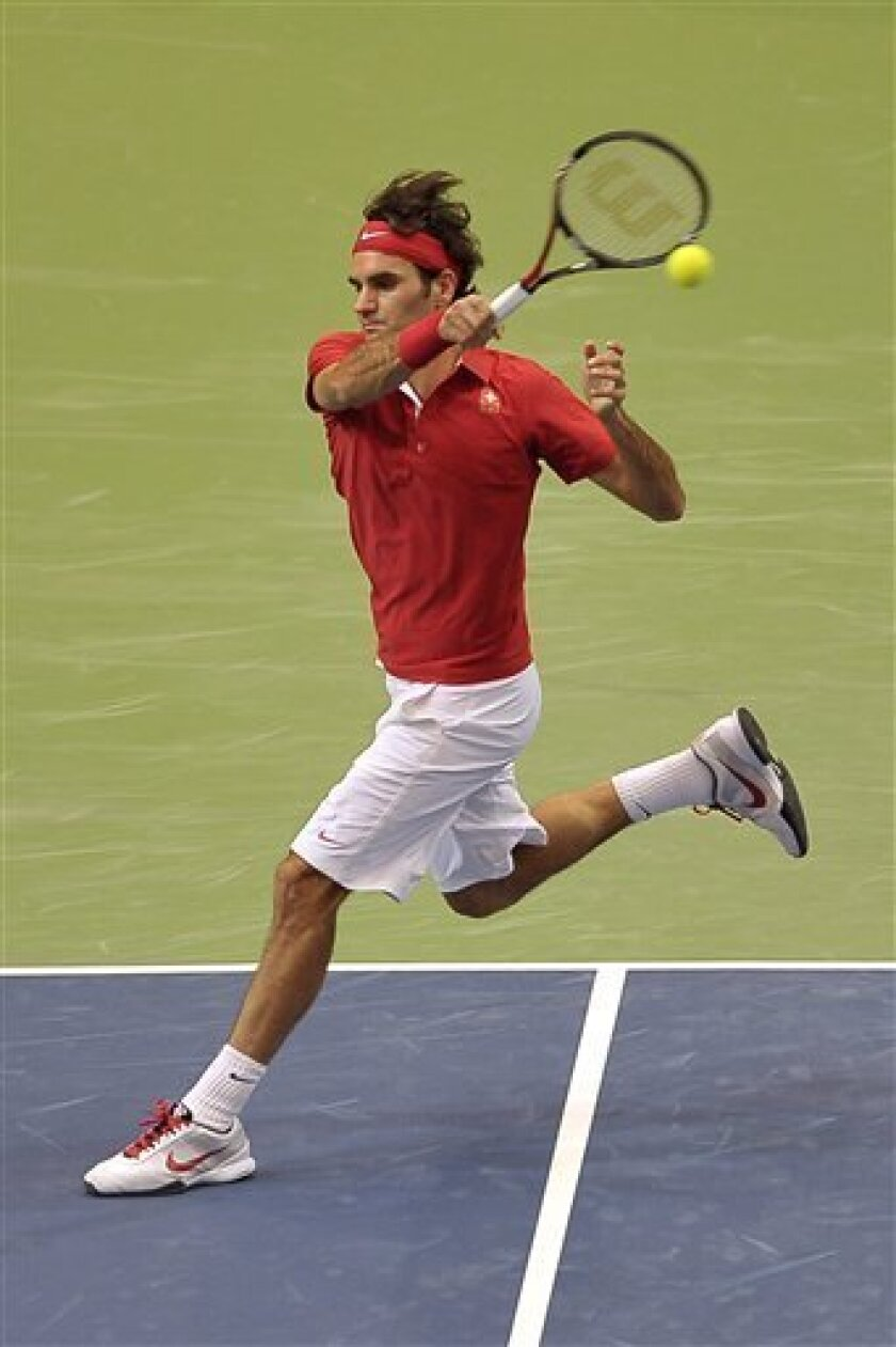 Roger Federer of Switzerland returns a ball to Rui Machado of Portugal during the Davis Cup Europe/Africa Zone Group I second round match in the Postfinance Arena in Bern, Switzerland, Friday, July 8, 2011. (AP Photo/Keystone/Dominic Favre) GERMANY OUT - AUSTRIA OUT