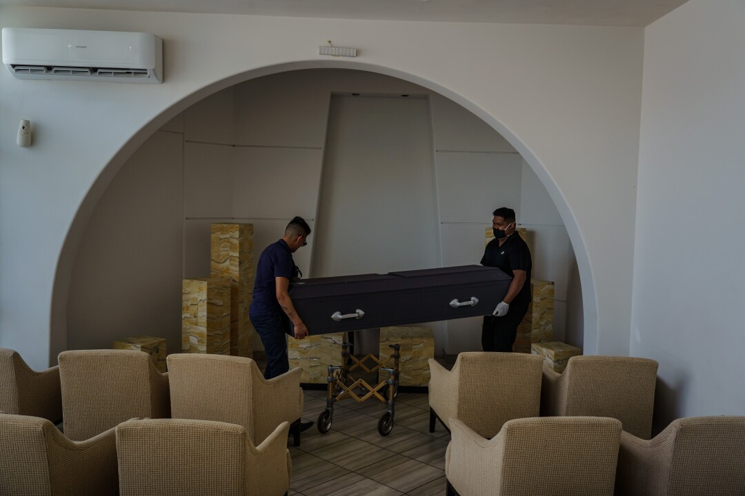 Workers at the San Ramon Funeral Home prepare a casket for transport to the cemetery.
