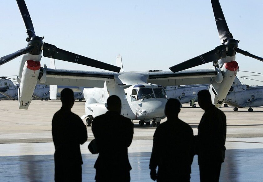 Marines keep an eye on a new MV-22 Osprey, which was displayed during a news conference at MCAS Miramar on Friday.