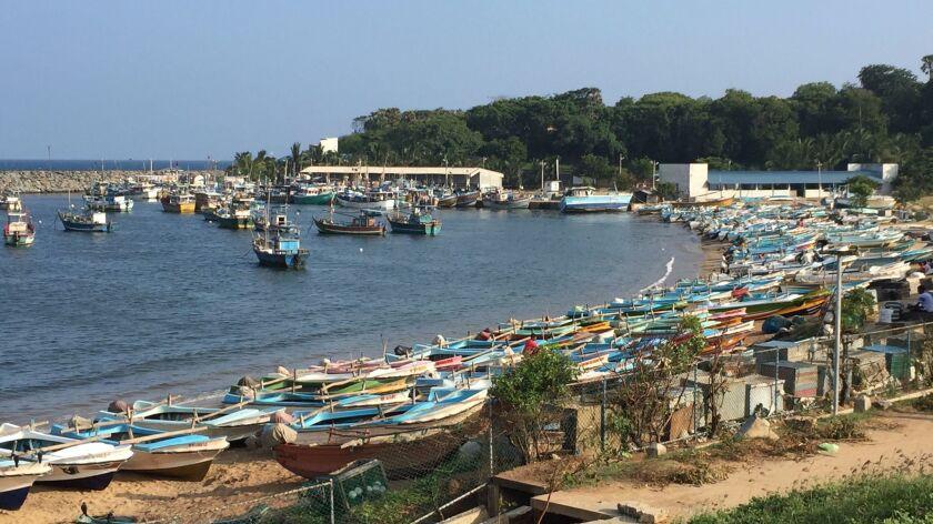 Fishing boats line the beach in downtown Hambantota, Sri Lanka.