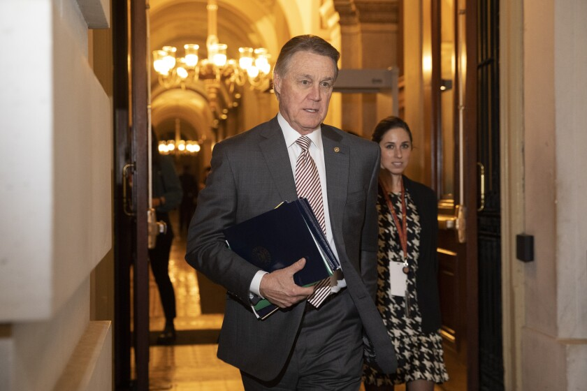 "FILE - In this Jan. 31, 2020, file photo, Sen. David Perdue, R-Ga., leaves Capitol Hill in Washington. Perdue has taken down a digital campaign ad featuring a manipulated picture of his Demoncratic opponent, Jon Ossoff, who is Jewish, with an enlarged nose. A spokeswoman for Perdue said in a statement Monday, July 27, 2020, that the image has been removed from Facebook, calling it an ""unintentional error"" by an outside vendor, without naming the vendor. (AP Photo/Jacquelyn Martin, File)"