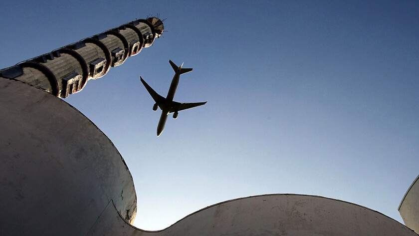 A jetliner flies over Academy Cathedral in Inglewood, not far from a proposed NFL stadium.