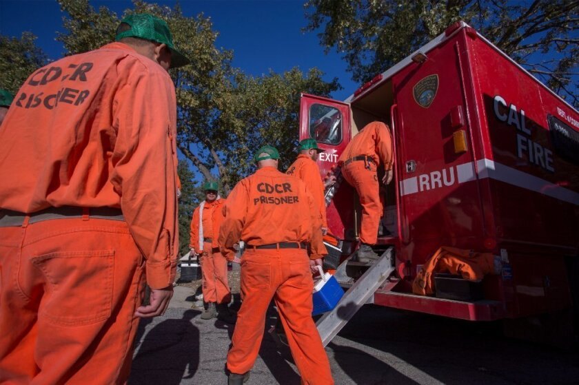 Prisoners at Oak Glen Conservation Camp leave the minimum security prison for work deployment under the authority of Cal Fire, during which time they are called and treated as firefighters rather than inmates until they return to camp, on Sept. 28, 2017 near Yucaipa, California.