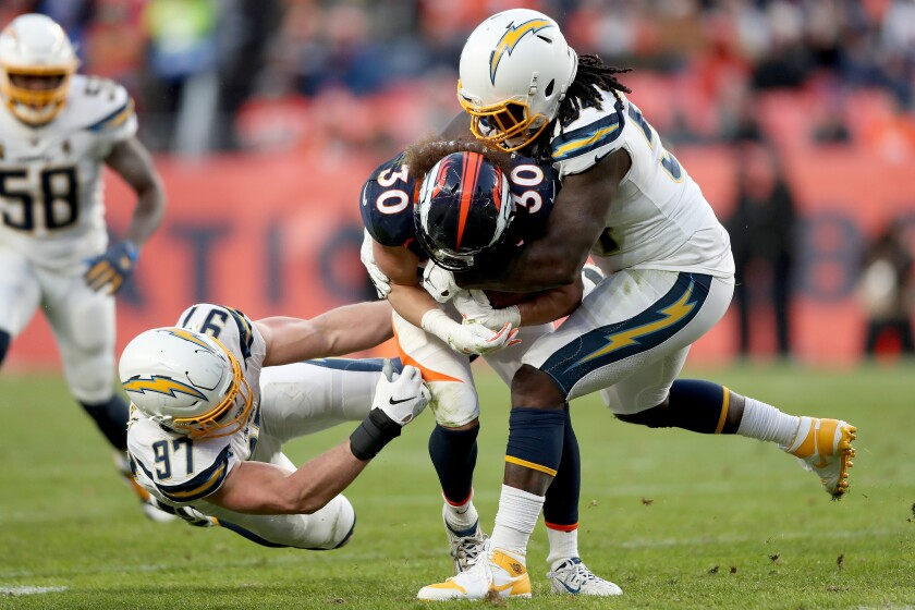 Denver Broncos' Phillip Lindsay (30) is tackled by Chargers' Joey Bosa (97) and Melvin Ingram III (54) in the third quarter on Sunday in Denver.