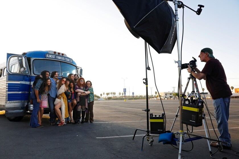 """Neal Preston (right) photographs the cast of the Old Globe production of """"Almost Famous"""" in the parking lot of Pechanga Arena San Diego (the venue formerly known as the San Diego Sports Arena)."""