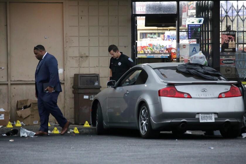 Detectives on Friday investigate the scene of a police shooting outside a San Bernardino liquor store.