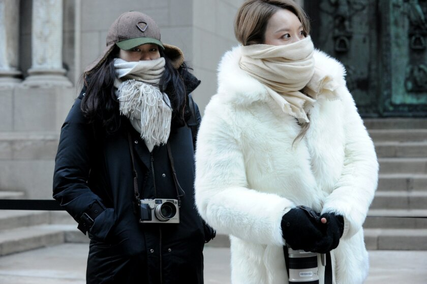 Street photographers brave the cold to photograph guests arriving to the Alexander Wang Fall 2016 show during Fashion Week, Saturday, Feb. 13, 2016, in New York. Bitter temperatures and biting winds had much of the northeastern United States bundling up for the some of the worst cold of the winter