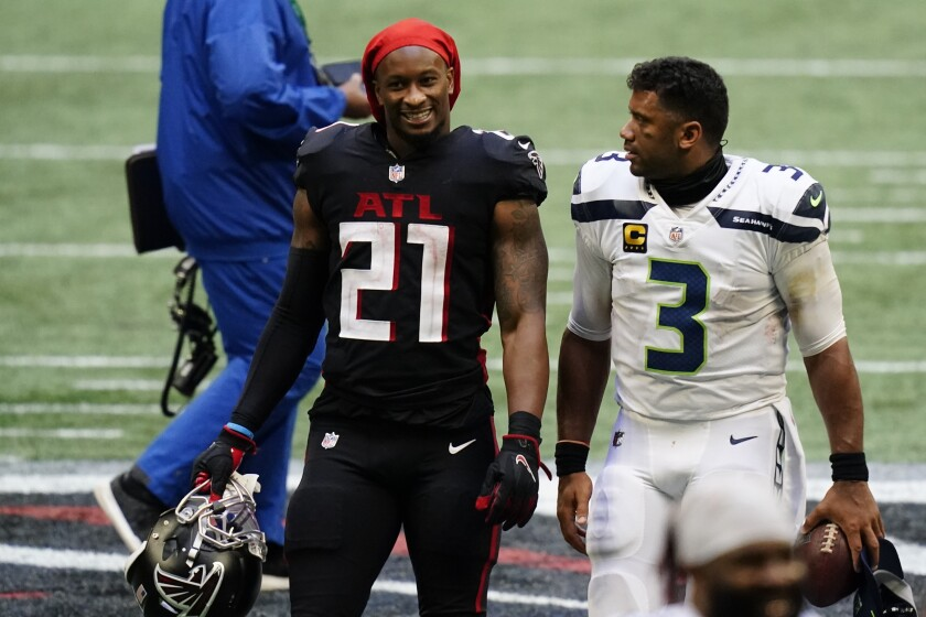Atlanta Falcons running back Todd Gurley, left, speaks with Seattle Seahawks quarterback Russell Wilson after the second half of an NFL football game, Sunday, Sept. 13, 2020, in Atlanta. The Seattle Seahawks won 38-25. (AP Photo/Brynn Anderson)