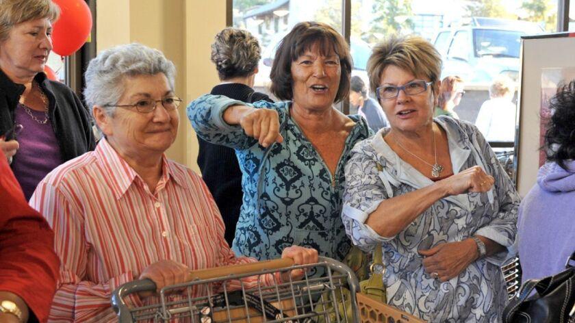 L–RArpi Shahinian (pushing cart) with singing shoppers Darlene Pittman and Sandy Wise.
