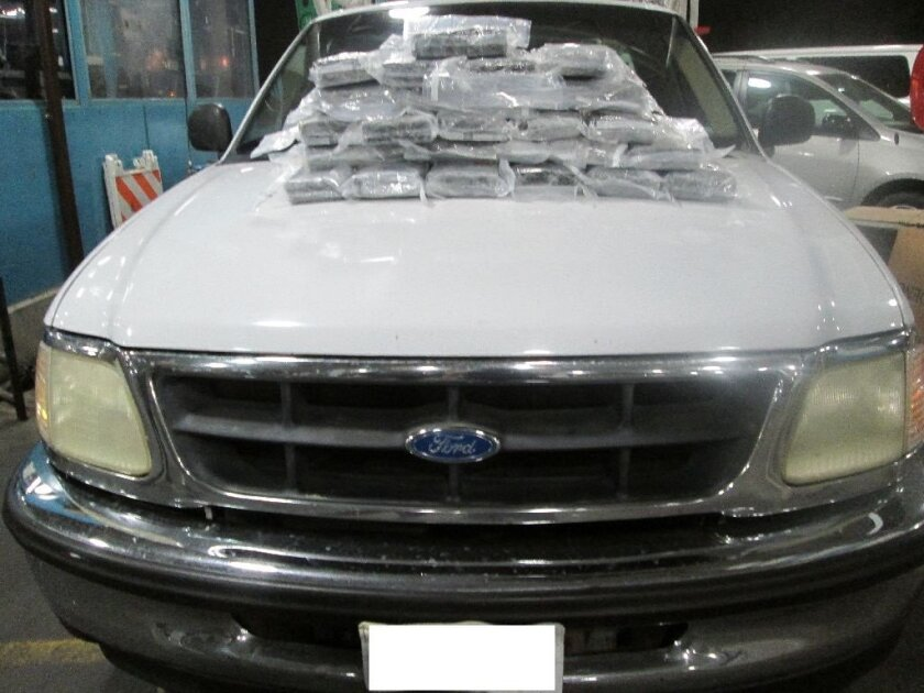 The 43 packages of cocaine seized from this Ford pickup at the Otay Mesa Port of Entry are displayed on the truck's hood.