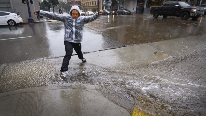 SAN DIEGO, CA 1/31/2019: A pedestrian does the best he can to stay dry as he jumps over rainwater f