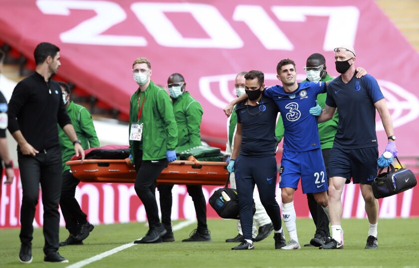 Chelsea's Christian Pulisic is assisted from the field after getting injured during the FA Cup final soccer match between Arsenal and Chelsea at Wembley stadium in London, England, Saturday, Aug. 1, 2020. (Adam Davy/Pool via AP)