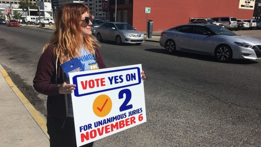 New Orleans resident Molly Ezell holds a sign promoting Amendment 2 in Louisiana.