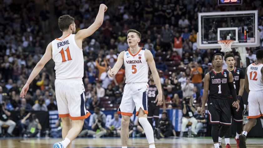 Virginia guard Kyle Guy (5) and Ty Jerome (11) celebrate after a score against Gardner-Webb during a