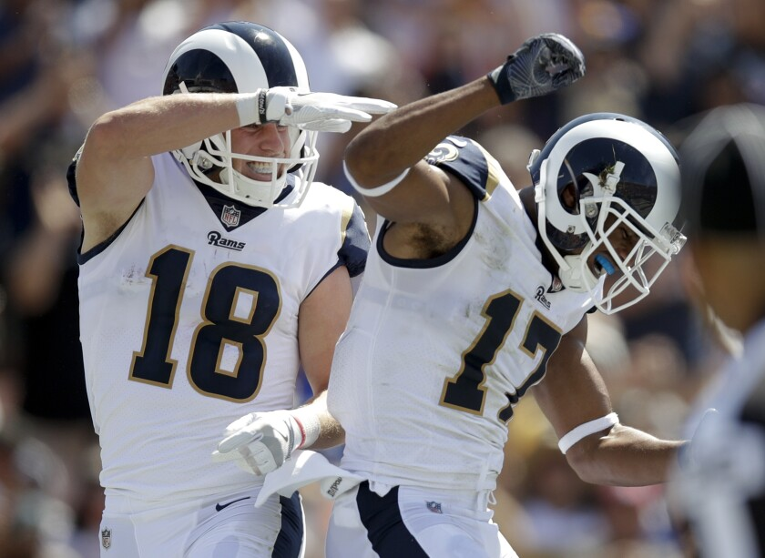 FILE - In this Sept. 10, 2017, file photo, Los Angeles Rams wide receiver Cooper Kupp, left, celebrates his touchdown with wide receiver Robert Woods during the first half of an NFL football game against the Indianapolis Colts in Los Angeles. Kupp and Woods spent the offseason getting kicked off various high school football fields while trying to get in some COVID-clandestine workouts. (AP Photo/Jae C. Hong, File)