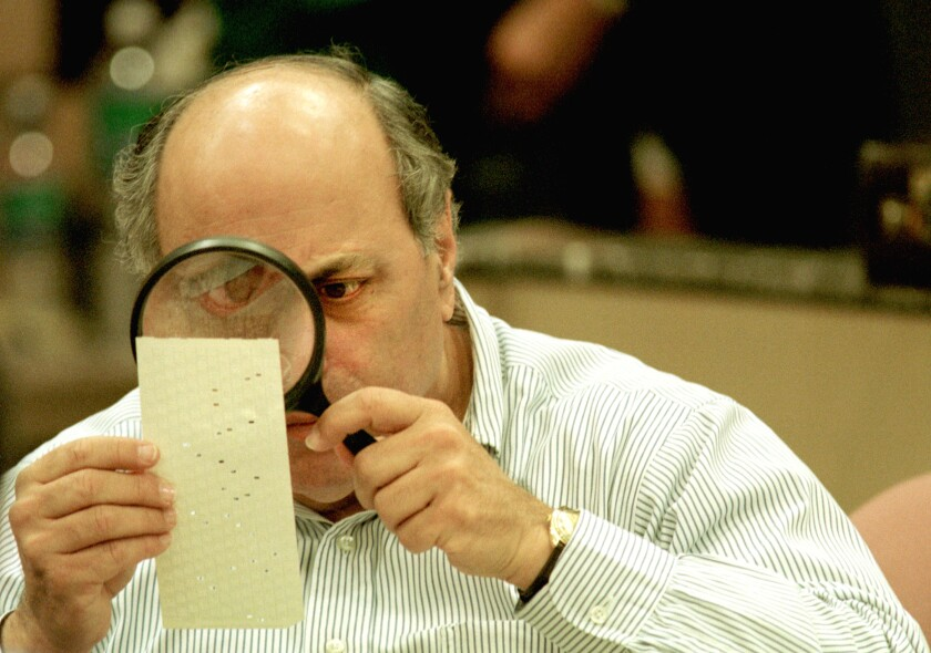 A man with a magnifying glass examines holes punched in a ballot card