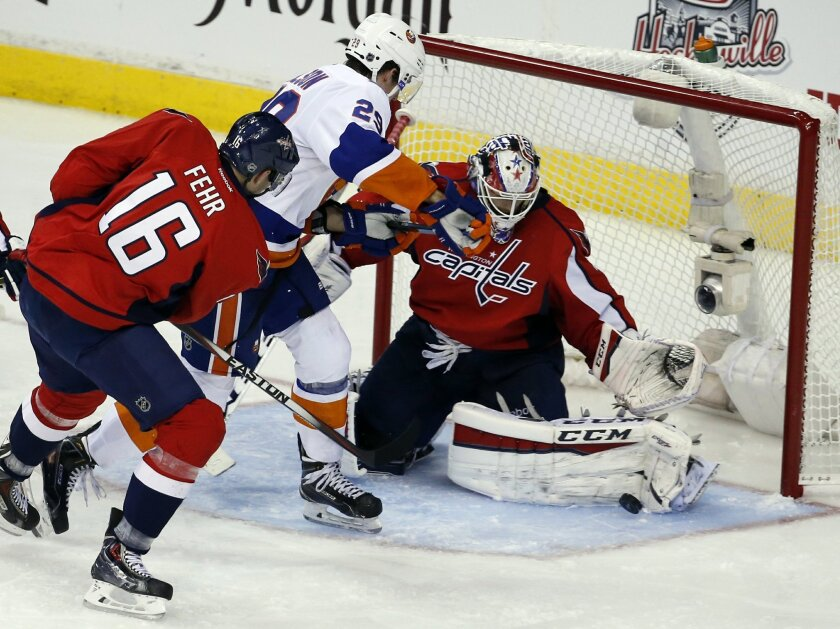 Washington Capitals right wing Eric Fehr (16) defends with goalie Braden Holtby (70) as New York Islanders center Brock Nelson (29) works in front of the net during the third period in the opening game of a first-round NHL hockey playoff series, Wednesday, April 15, 2015, in Washington. The Islande