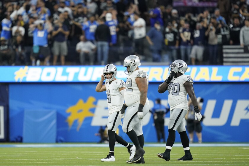 Las Vegas Raiders quarterback Derek Carr, left, and teammates walk off the field after an interception during the second half of an NFL football game against the Los Angeles Chargers, Monday, Oct. 4, 2021, in Inglewood, Calif. (AP Photo/Ashley Landis)
