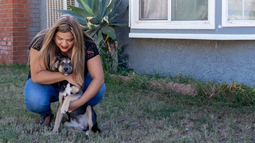 Marcela Villa plays with her dog at her home in Corona. Villa says her job at the company now called Agilon Health was to determine whether patients' care should be covered. She was later fired.