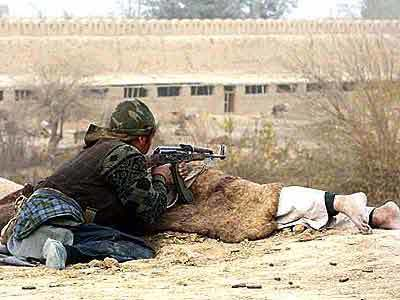A Northern Alliance fighter seeks cover behind a corpse