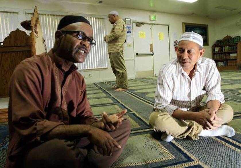 Community member Aaron Goulding, left, and President Krya Jacques of the Cham American Muslim Community in Pomona talk about the terror suspects arrested last Friday.