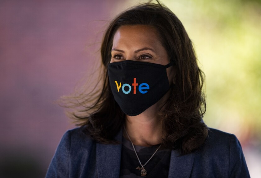 "Michigan Gov. Gretchen Whitmer wears a mask with the word ""vote"" on it during a healthcare discussion Wednesday in Kalamazoo"