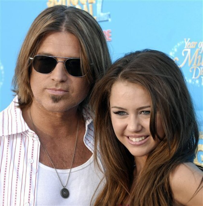 "This Aug. 14, 2007 file photo shows singer Billy Ray Cyrus, left, and his daughter Miley Cyrus, pose together at the premiere of Disney Channel's ""High School Musical 2"" in Anaheim, Calif. The teen sensation writes in her memoir, ""Miles to Go,"" that negative reactions to her bond with her father a"