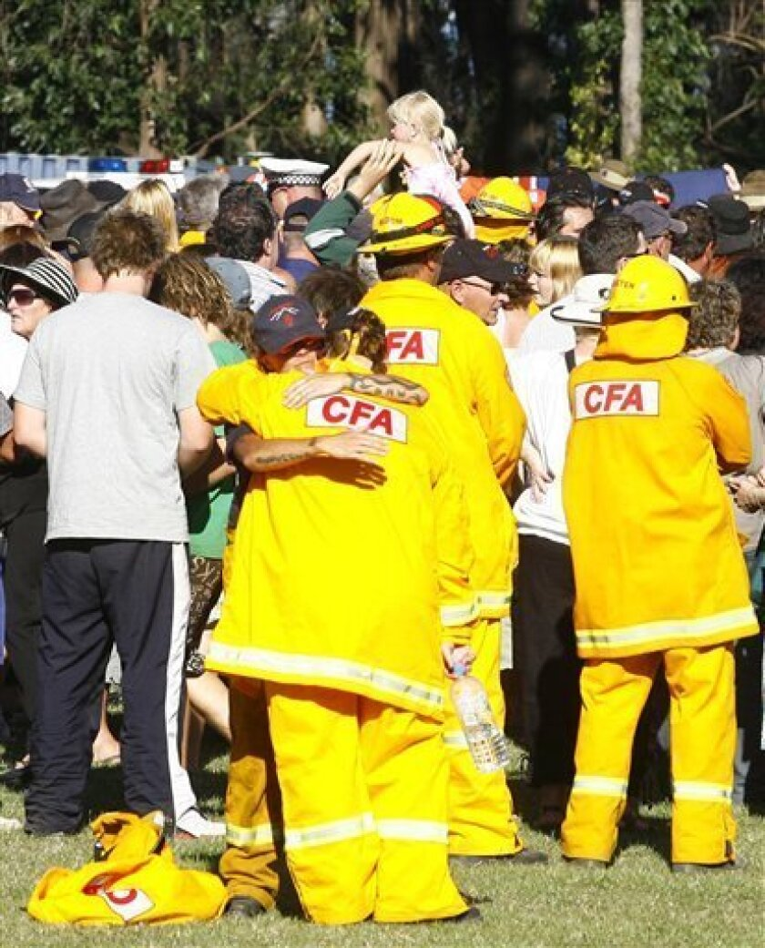 Residents from the town of Kinglake gather to thank firefighters during a one-year anniversary memorial in Kinglake, Australia Sunday, Feb. 7, 2010. A remembrance service was held to honor the 173 people killed during the Feb 7, 2009 fires. (AP Photo/Paul Jones)