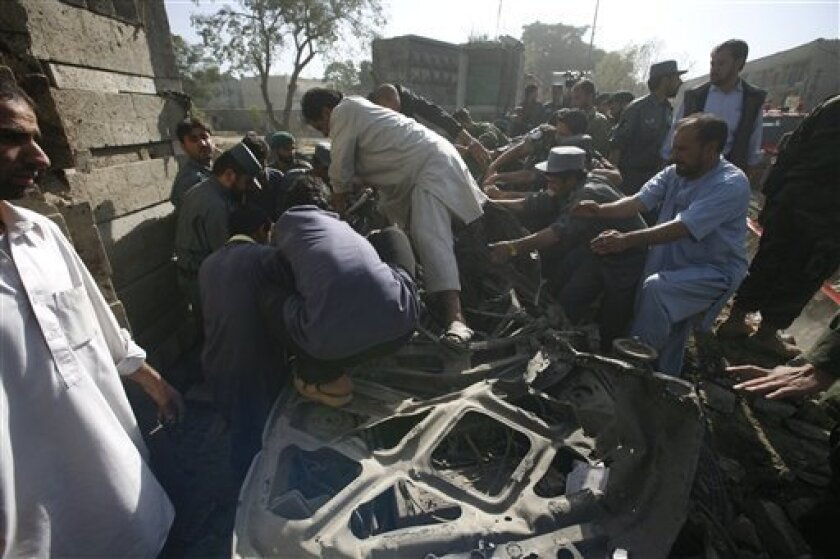Afghans try to take a victim out of a car at the site of a blast in Kabul, Afghanistan on Thursday, Oct. 8, 2009. The powerful explosion rocked the center of Afghanistan's capital early Thursday near the Interior Ministry and the Indian Embassy, where dozens of civilians were killed in an attack last year. (AP Photo/Musadeq Sadeq)