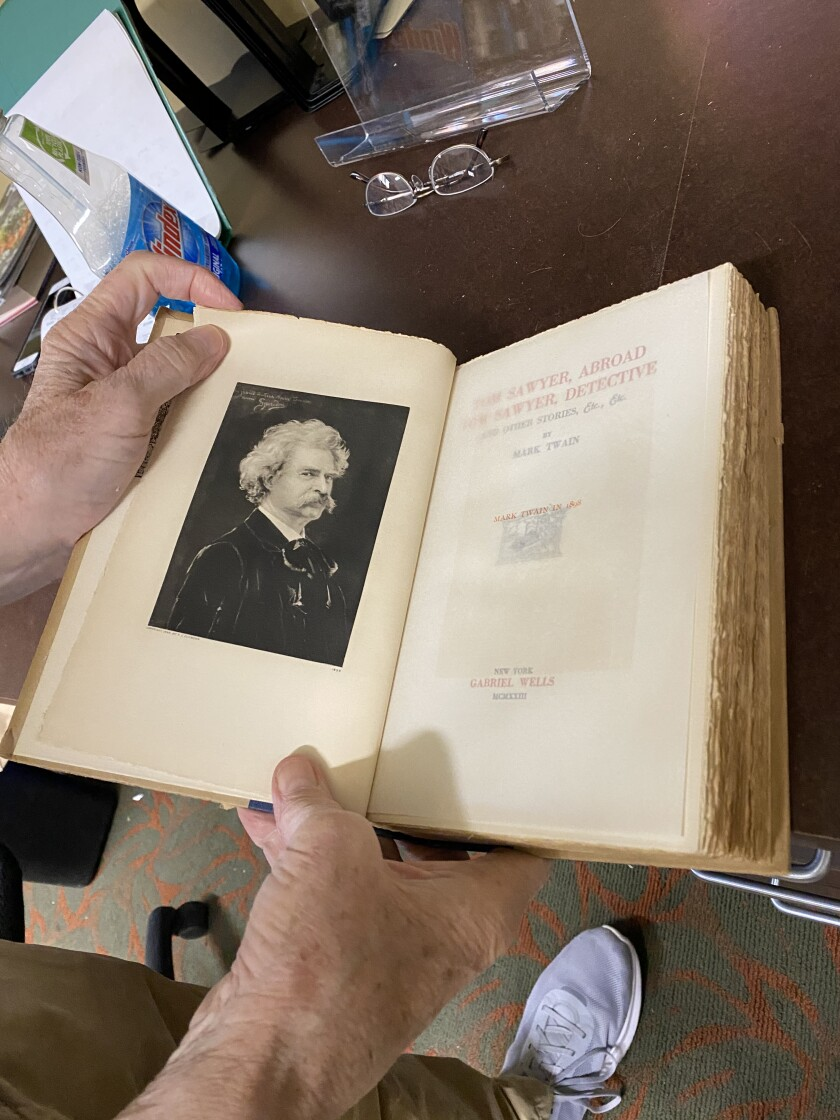 Volunteer Jim Stewart holds open one book in a 15-volume Mark Twain set recently donated to the library by an anonymous donor.