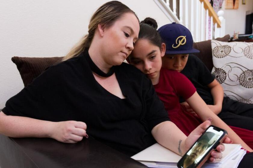 La estadounidense Christine Palomar (i) habla a través de un teléfono junto a sus hijos Joshua (c) y April (d), el 31 de julio de 2019, con su esposo, el mexicano José Palomar, quien fue obligado a permanecer en México después de que se le negara una solicitud de residencia permanente en EEUU. EFE/Felipe Chacón