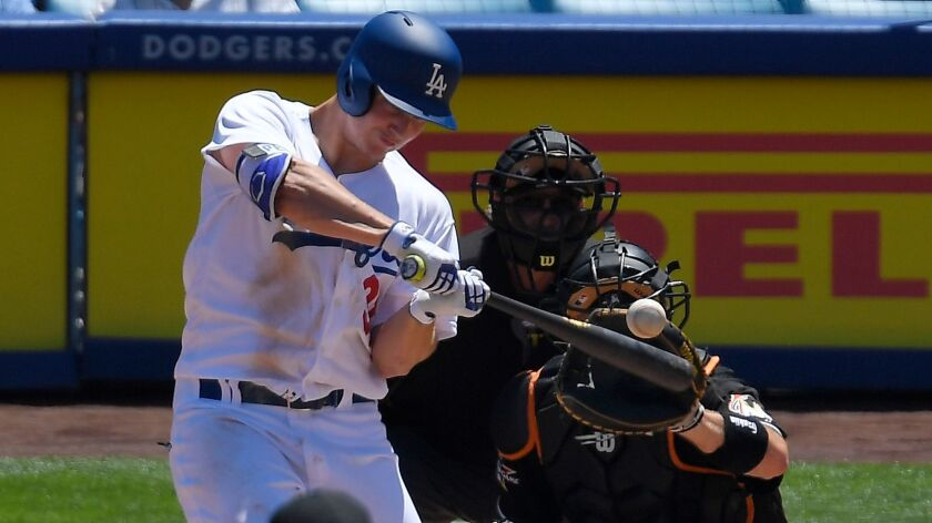 Los Angeles Dodgers' Joc Pederson, left, hits a solo home run as Miami Marlins catcher A.J. Ellis, r