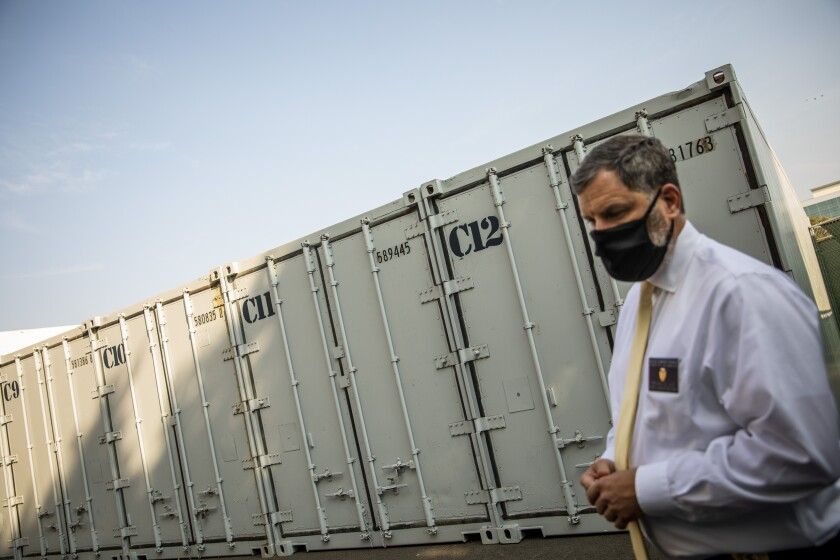 A man in front of a freezer container