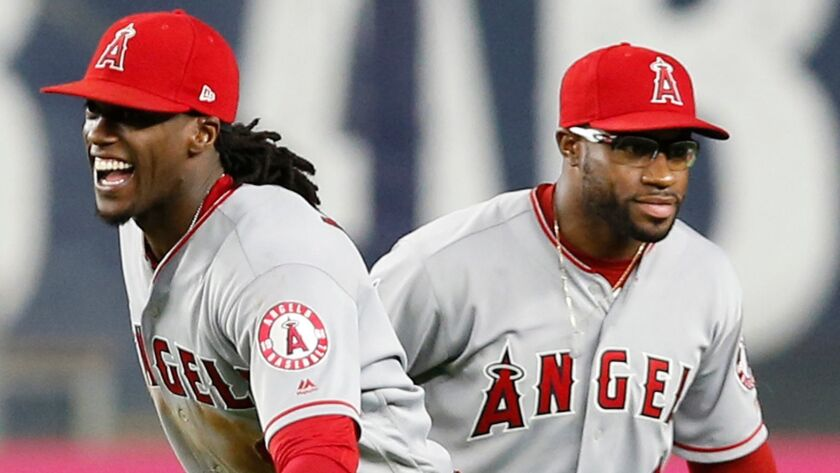Los Angeles Angels center fielder Cameron Maybin, left, and Angels left fielder Eric Young Jr. celeb