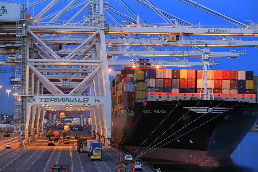 Trucks haul loads as containers are unloaded from a ship at the Port of Los Angeles.
