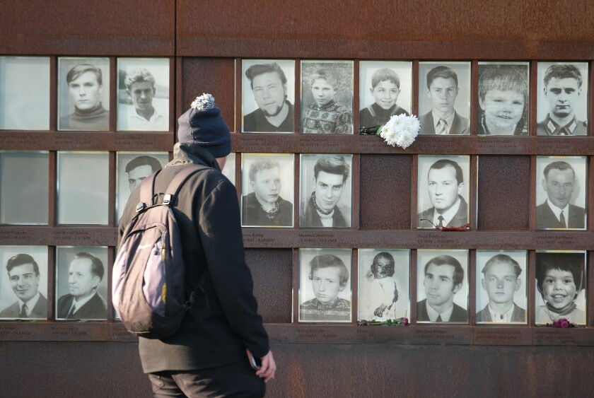 A visitor looks at a memorial to people who died trying to breech the Berlin Wall at the Bernauer Strasse memorial site in Berlin, Germany.